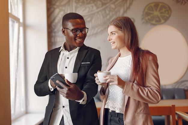 Personas internacionales de pie en una cafetería y tomando un café