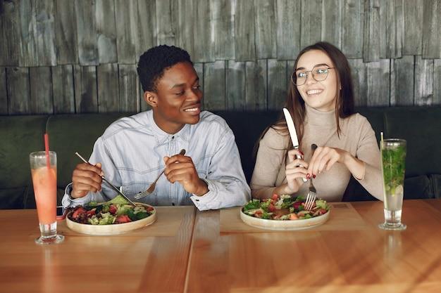 Personas internacionales sentados a la mesa con ensaladas y cócteles.