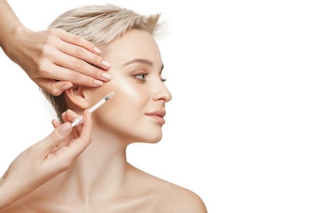Personas, labios, cosmetología, cirugía plástica y concepto de belleza - rostro y mano de mujer joven hermosa con jeringa haciendo inyección