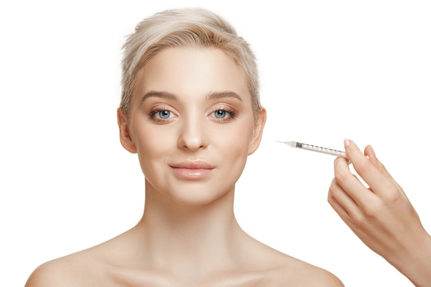 Personas, labios, cosmetología, cirugía plástica y concepto de belleza - rostro de mujer joven hermosa y mano con inyección de jeringa
