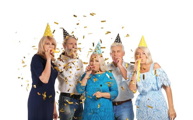 Personas maduras en sombreros de fiesta de cumpleaños con silbidos sobre superficie blanca