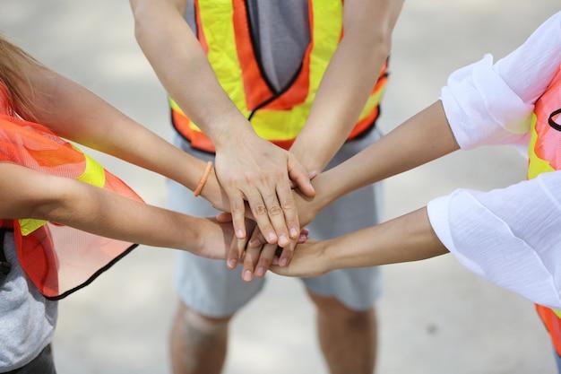 Personas con las manos unidas en equipo.