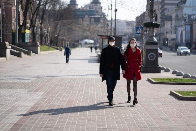 Personas en máscaras de protección facial en una calle casi vacía