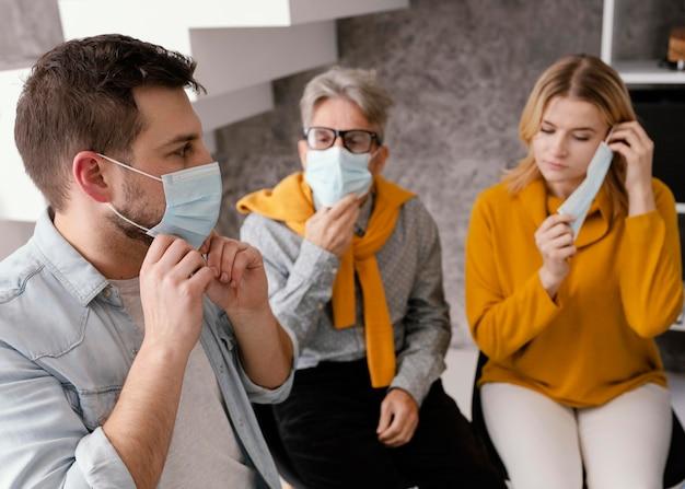 Personas con máscaras en terapia de grupo.