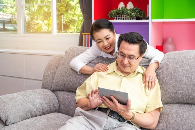 Personas mayores asiáticas, abuelos con tableta digital en el hogar, familia feliz con concepto de tecnología