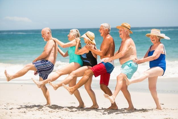 Personas mayores bailando en una fila en la playa.