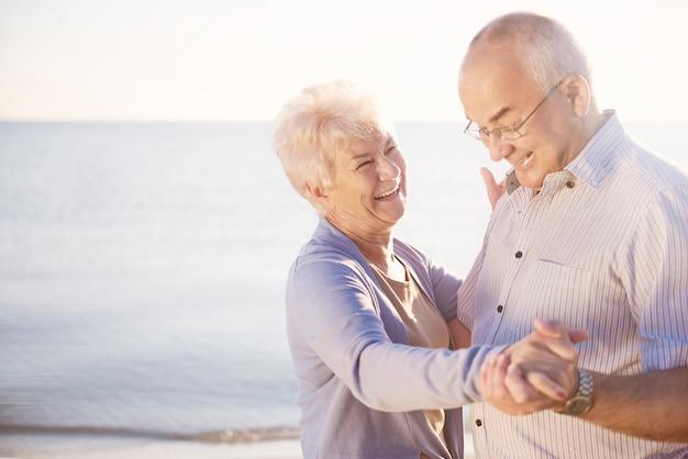 Personas mayores bailando en la playa de buen humor