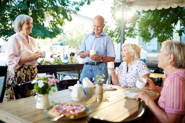 Personas mayores celebrando vacaciones en café