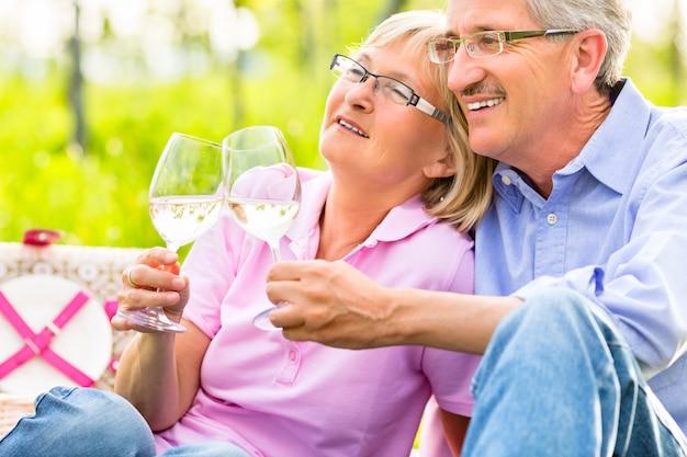 Personas mayores felices haciendo picnic bebiendo vino