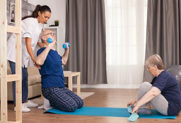 Personas mayores haciendo deporte con fisioterapeuta en casa.