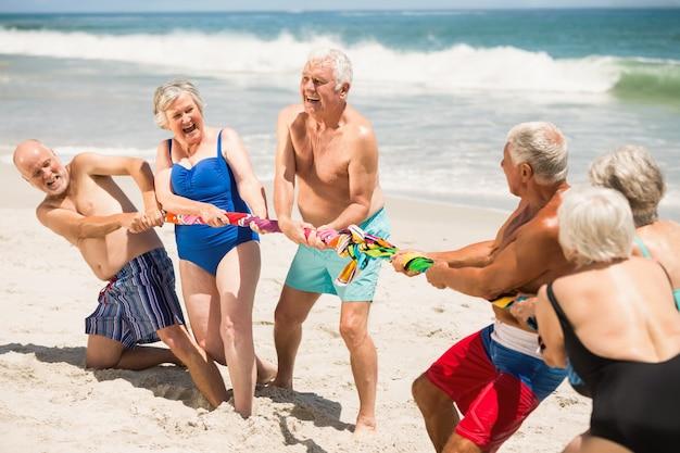 Personas mayores jugando tira y afloja en la playa