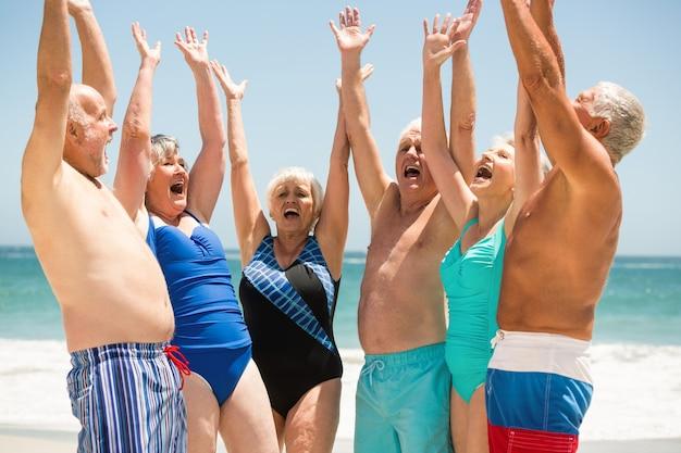 Personas mayores con las manos arriba en la playa.