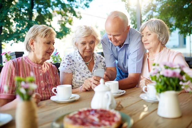 Personas mayores modernas con teléfono inteligente