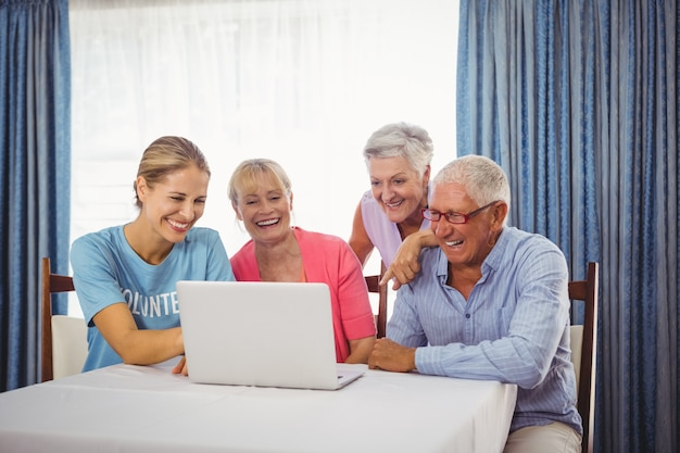 Personas mayores y mujer usando laptop
