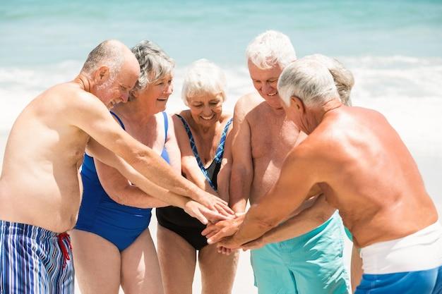 Personas mayores de pie en un círculo en la playa.