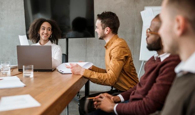 Personas en la mesa de la oficina durante una reunión.