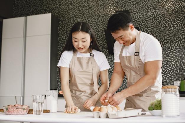 Personas mientras preparan bolas de masa hervida. gente asiática en delantales.