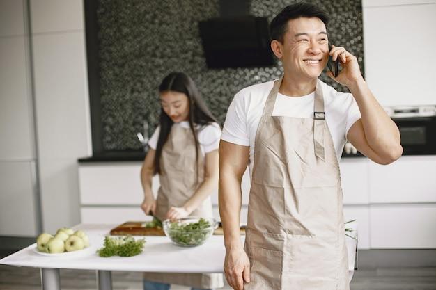 Personas mientras preparan ensalada de verduras frescas. gente asiática en delantales.