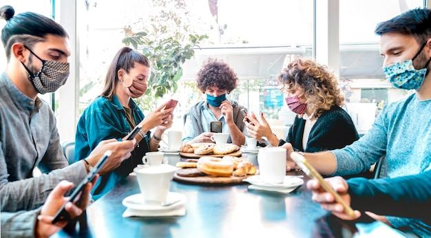 Personas milenarias que utilizan teléfonos móviles inteligentes en la barra de café - centrarse en el tipo de marco central