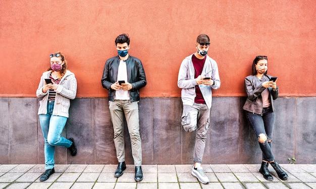 Personas milenarias que utilizan teléfonos móviles inteligentes cubiertos por mascarilla