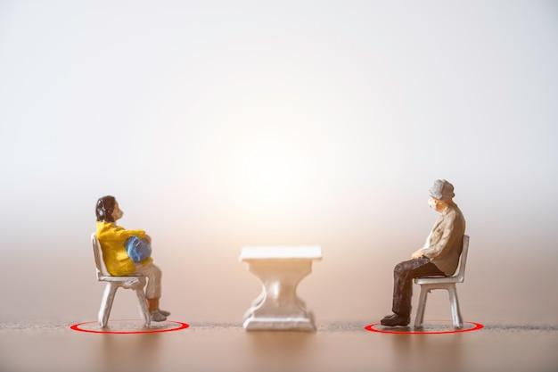 Las personas en miniatura de anciano y mujer que usan mascarilla y se sientan en la silla se mantienen alejados en público para prevenir la infección pandémica del brote del virus de la corona covid-19.