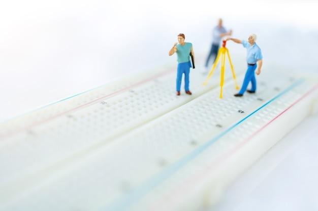 Personas en miniatura buscando o comprobando errores y problemas en el microchip, placa base de la computadora.