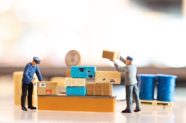 Personas en miniatura cartero oficial de guardia, se prepara para enviar una caja al consumidor. servicio de entrega para el concepto de comercio electrónico