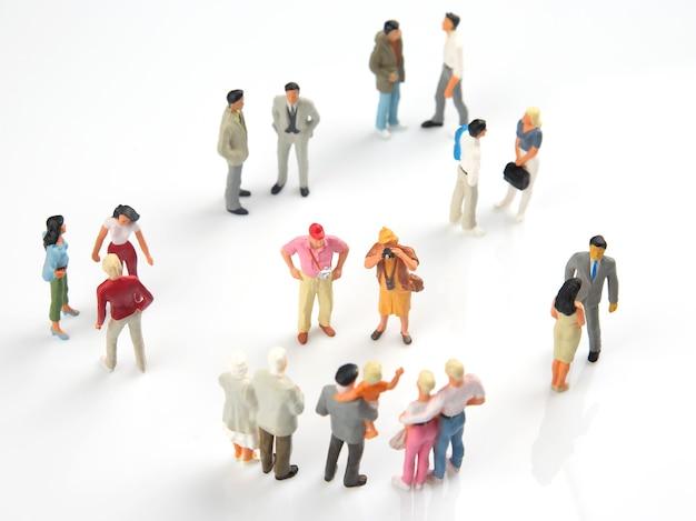 Las personas en miniatura se comunican entre sí sobre un fondo blanco.