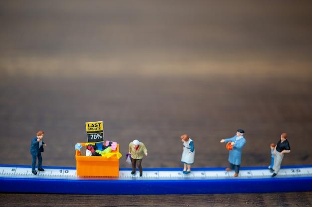 Las personas en miniatura mantienen distancia en el centro comercial y el área pública. concepto de distanciamiento social.
