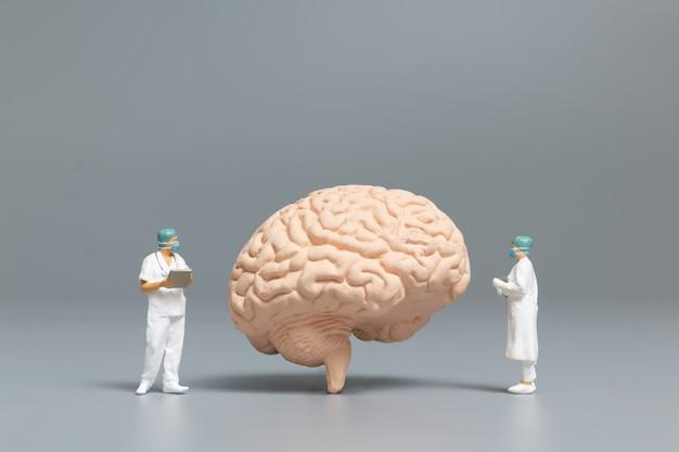 Personas en miniatura médico y enfermera observando y discutiendo sobre el cerebro humano, la ciencia y el concepto médico