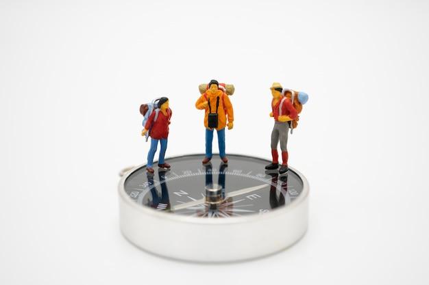 Las personas en miniatura se paran en la pasarela, el comienzo del viaje para llegar a la meta.