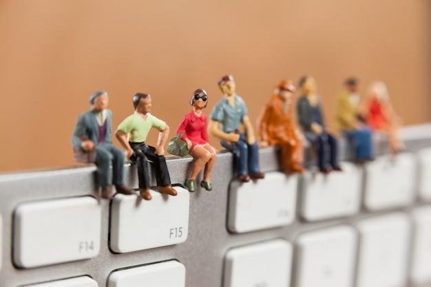 Las personas en miniatura sentado en la parte superior del teclado
