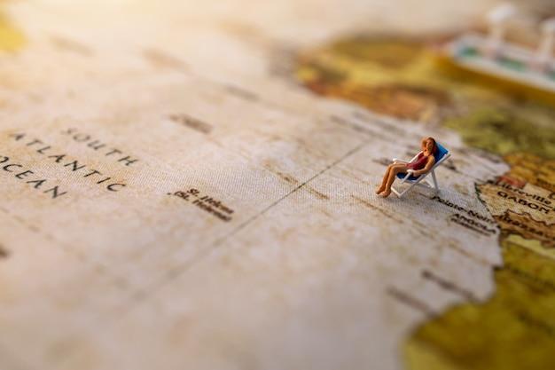 Las personas en miniatura se sientan en los asientos para tomar el sol en la playa en el mapa del mundo vintage y el concepto de barco, viaje y verano.
