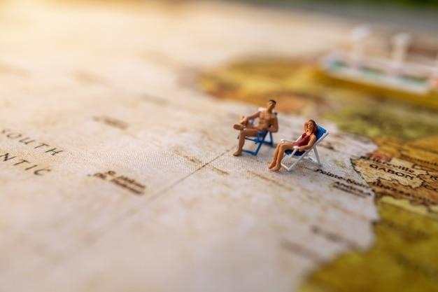 Las personas en miniatura se sientan en los asientos para tomar el sol en la playa en el mapamundi vintage y envían, concepto de verano