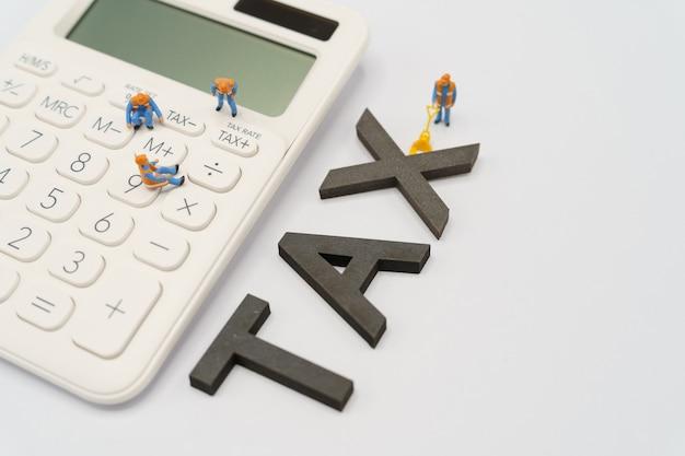 Personas en miniatura trabajador de la construcción teclado botón tax para el cálculo de impuestos