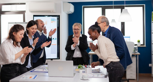 Personas motivadas del equipo de negocios diverso feliz aplaudiendo celebrando el éxito en la reunión corporativa