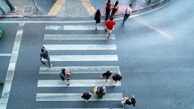 Las personas se mueven a través del paso de peatones en la carretera de la ciudad (en la vista superior).