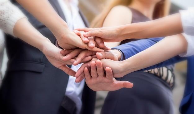 Las personas de negocios están uniendo sus manos para mostrar el espíritu en el lugar de trabajo.