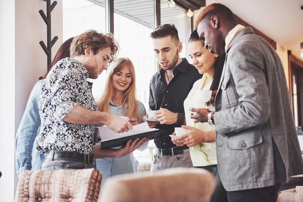 Las personas de negocios exitosas usan aparatos, hablan y sonríen durante la pausa para el café en la oficina