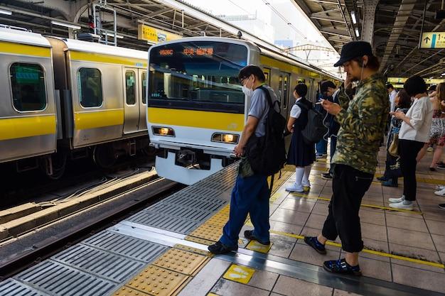 Personas no identificadas en la plataforma jr de la línea amarilla y azul local con trenes de llegada