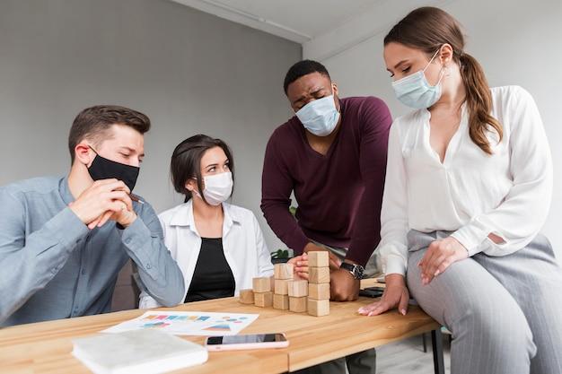Personas en la oficina durante una pandemia que tienen una reunión con máscaras médicas en