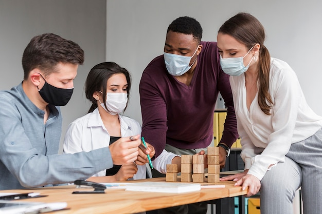 Personas en la oficina durante una pandemia que tienen una reunión con máscaras