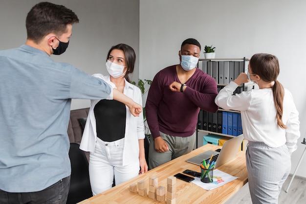 Personas en la oficina durante una pandemia reuniéndose y tocándose los codos