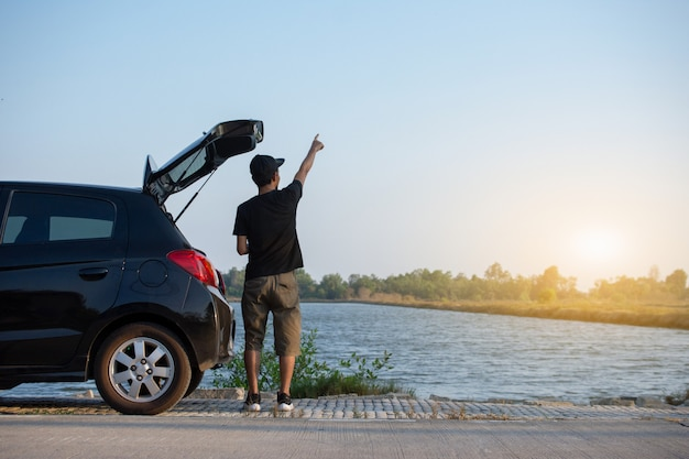 Personas de pie en el automóvil estacionado en la carretera