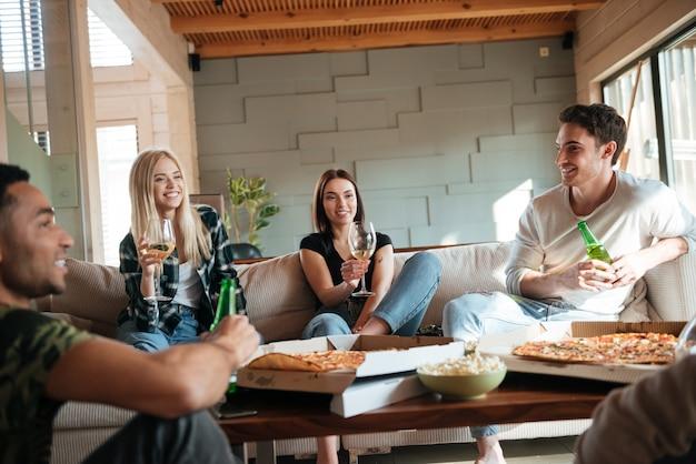 Personas con pizza, vino y cerveza sentados y hablando