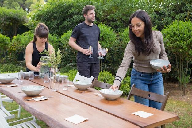 Personas positivas sirviendo mesa con platos al aire libre.