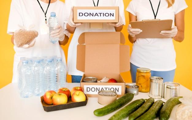 Personas preparando cajas de donaciones con provisiones para el día de la comida