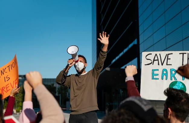 Personas en protesta ambiental con máscara.