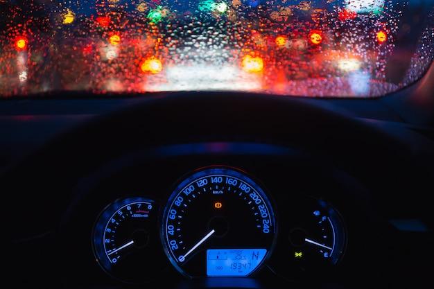 Personas que conducen el coche moderno en la noche con la luz y la gota de agua bokeh en llover día