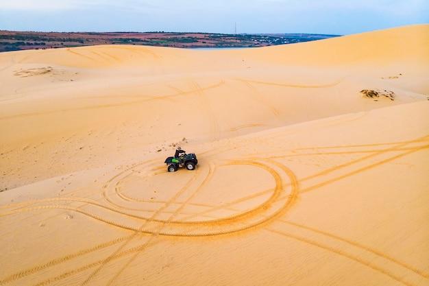 Personas que conducen en quad - ciclistas felices en el desierto de arena.